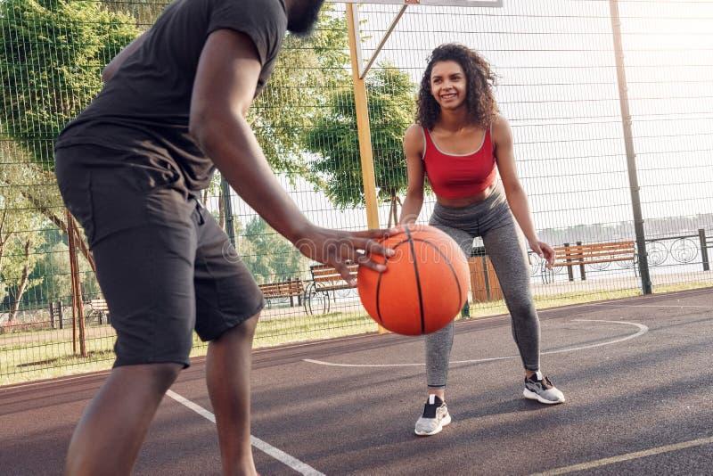 户外活动 非洲夫妇在球场上嬉戏、笑得开朗的女孩上打篮球 免版税库存图片