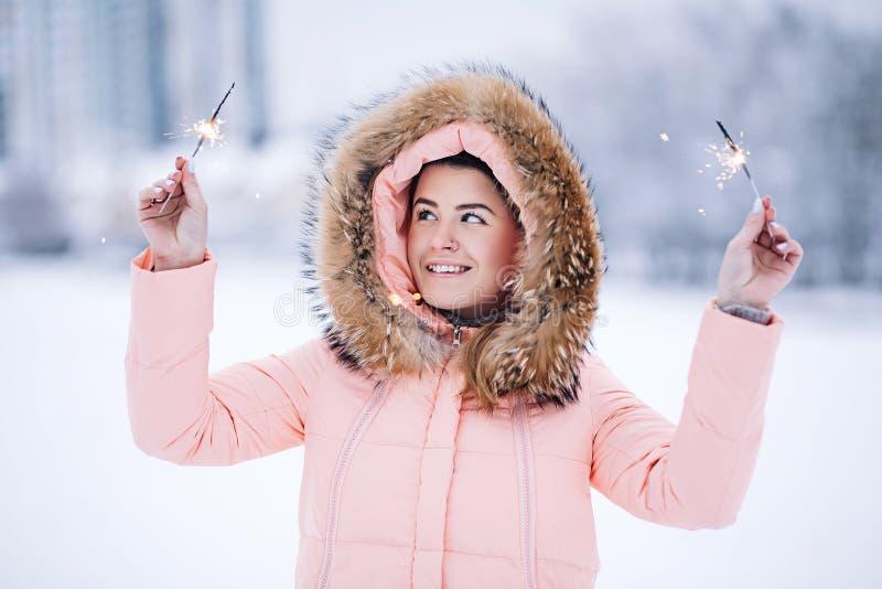 户外温暖的冬天夹克的微笑的愉快的俏丽的妇女享用冬天旅途、weared手套和敞篷,很多雪 库存照片