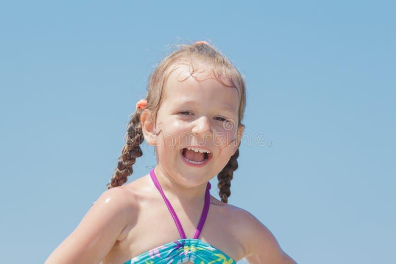 户外特写镜头使笑靠岸小女孩孩子画象  图库摄影