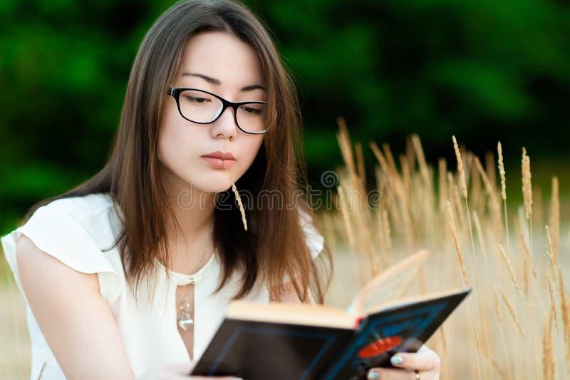 户外画象美丽的韩国女孩看书 免版税库存照片