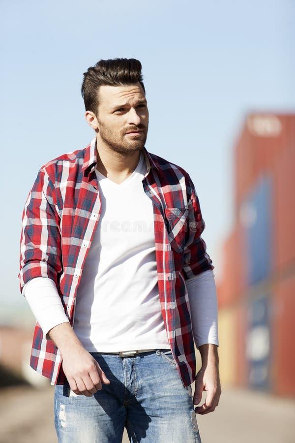 户外白色T恤杉、衬衣和牛仔裤的英俊的年轻人 免版税库存图片