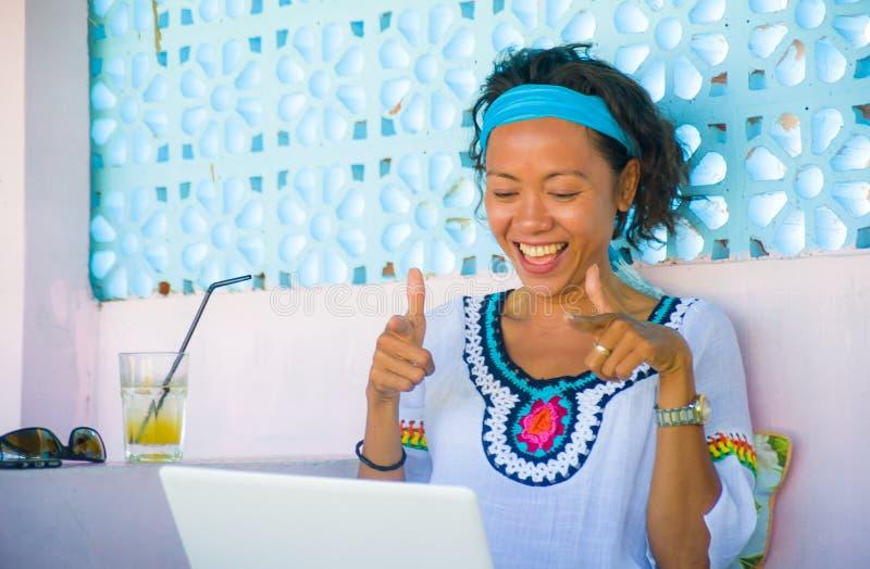 户外看妇女的年轻可爱和愉快的行家画象在网上与便携式计算机一起使用凉快的咖啡店作为s 免版税图库摄影