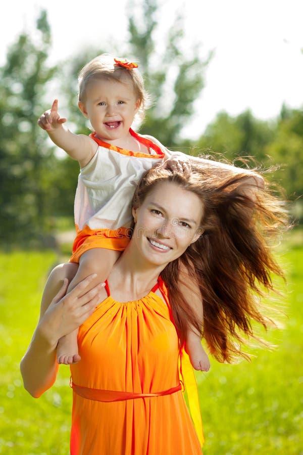 户外秀丽妈妈和婴孩 使用本质上的愉快的家庭 Mo 免版税库存图片