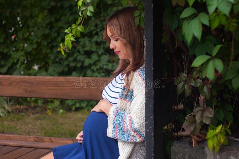户外秋天步行的美丽的白肤金发的白种人孕妇,握她的腹部用一个软,肉欲,产科方式 免版税库存图片