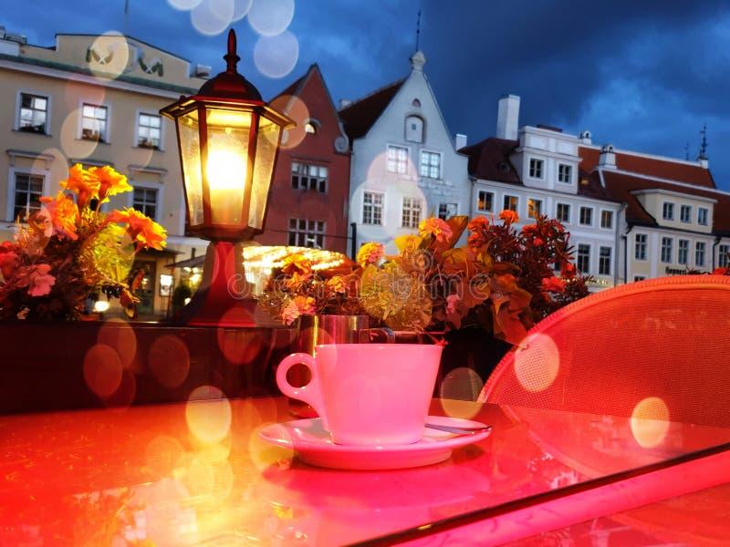 户外秋季橙色背景咖啡桌街咖啡杯咖啡杯,咖啡夜城灯光模糊夜城我 免版税图库摄影