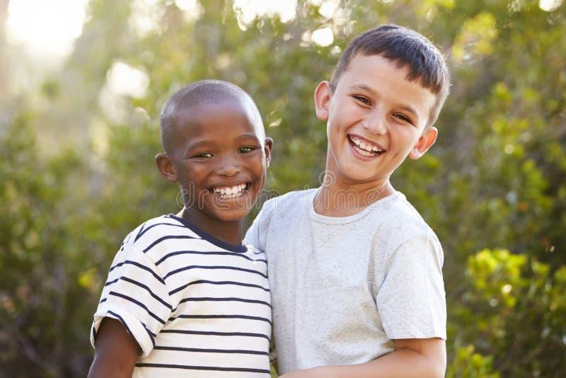 户外笑和看对照相机的两个男孩画象  免版税库存图片