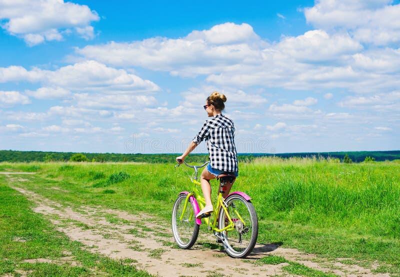 户外美丽的女孩骑马自行车 库存图片