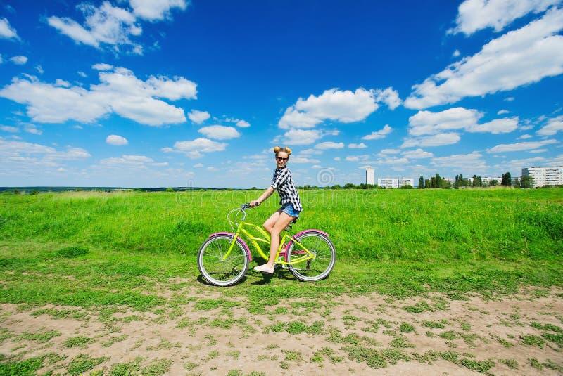 户外美丽的女孩骑马自行车 免版税图库摄影