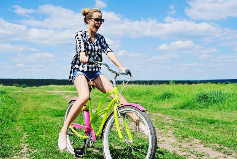 户外美丽的女孩骑马自行车 库存照片
