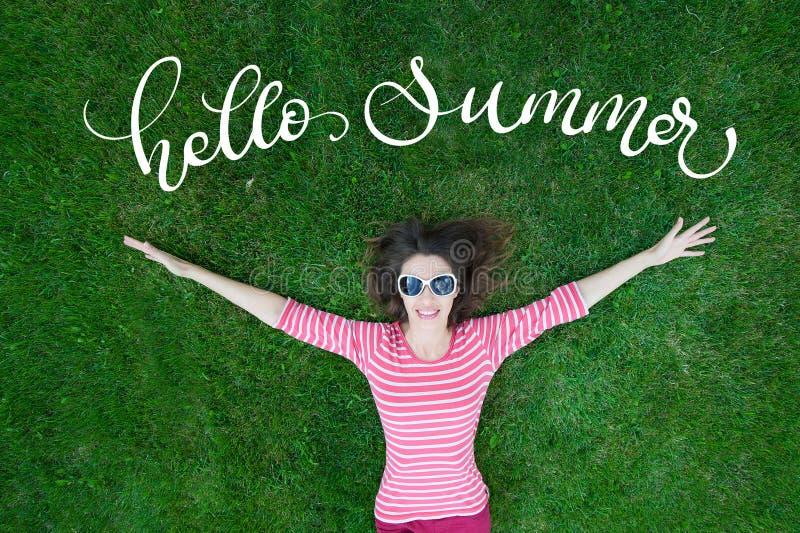 户外美丽的少妇在绿草和文本你好夏天 书法字法 免版税库存照片