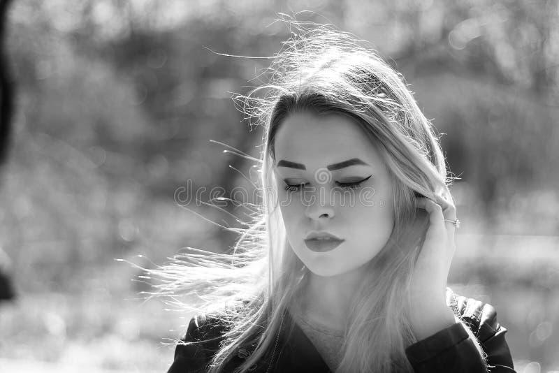户外美丽的新深色的女孩纵向 妇女微笑愉快在晴朗的夏天或春日外面在城市背景 免版税库存照片