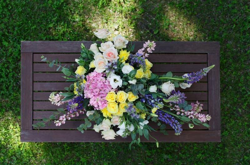 户外美丽的花花束在木台式视图 免版税库存照片