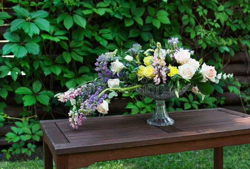 户外美丽的花花束 婚姻的植物的装饰在木桌上 库存图片