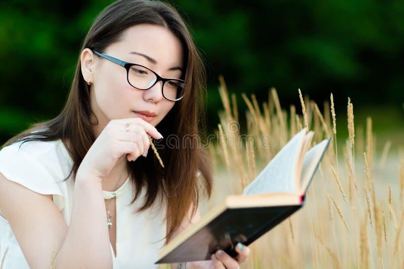 户外美丽的韩国女孩看书 图库摄影