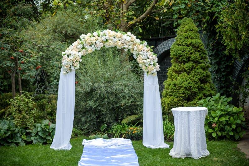 户外美好的婚礼 在草的装饰的椅子立场 婚姻的曲拱由布料和白色和桃红色花制成  免版税库存图片