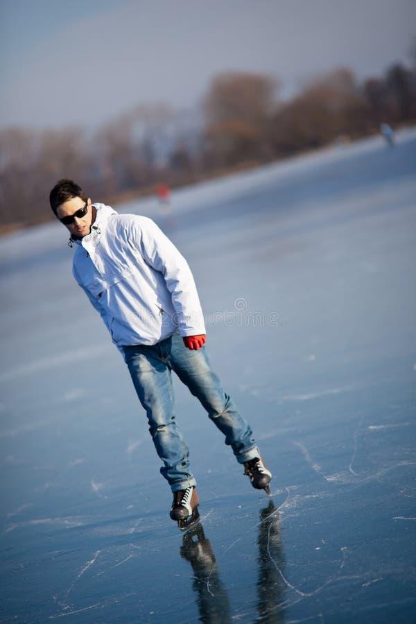 户外英俊的冰人筑成池塘滑冰的年轻人 免版税图库摄影