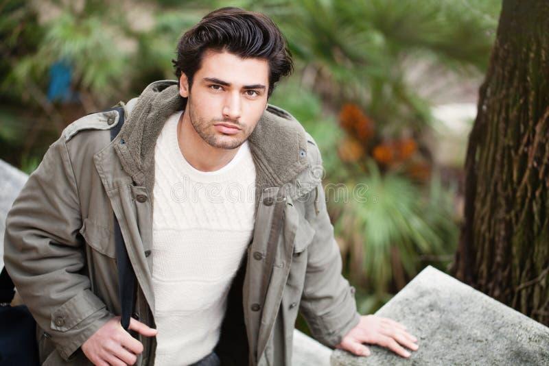 户外英俊的年轻意大利人、时髦的头发和外套 免版税库存照片
