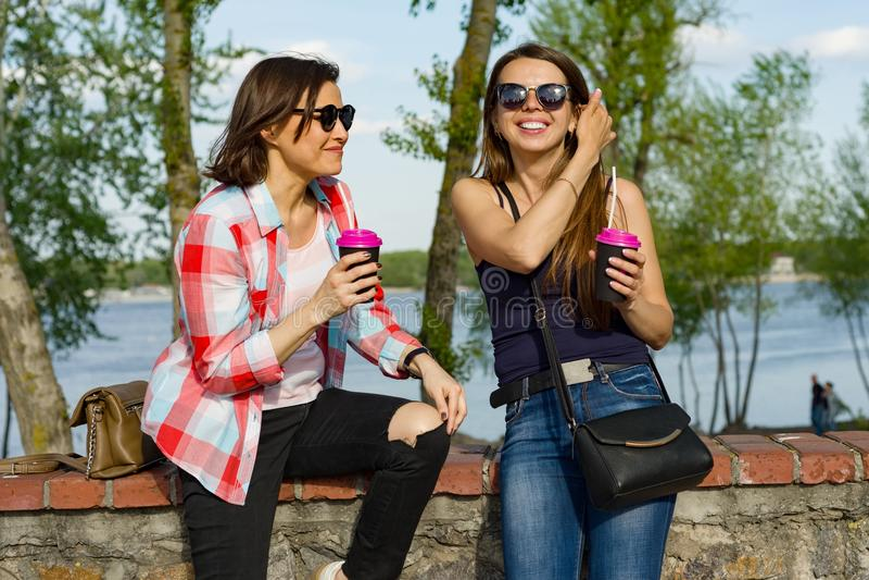 户外获得女性的朋友画象喝咖啡和乐趣 背景自然,公园,河 都市生活方式和友谊 免版税库存图片
