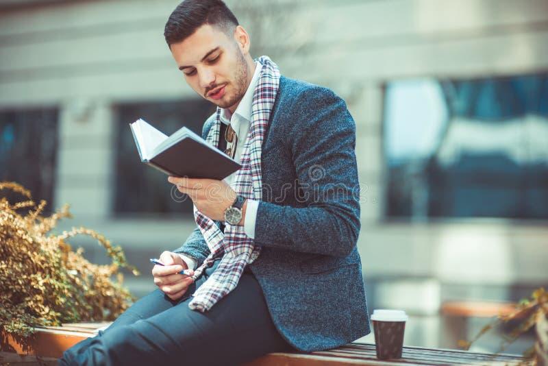户外衣服的人,读一本书用他的咖啡在他附近 免版税库存照片