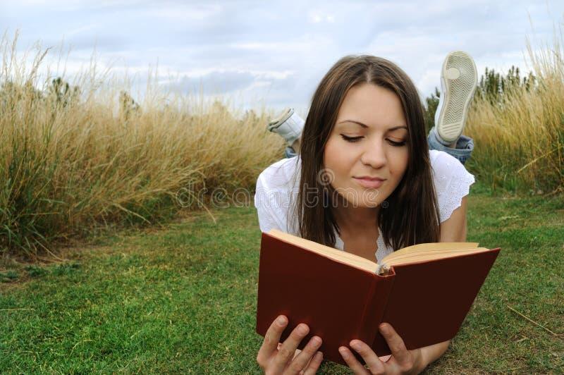 户外读妇女的书 免版税库存照片