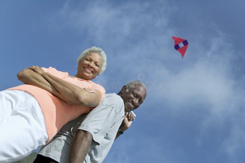 户外资深夫妇飞行风筝(低角度视图) (画象) 库存照片