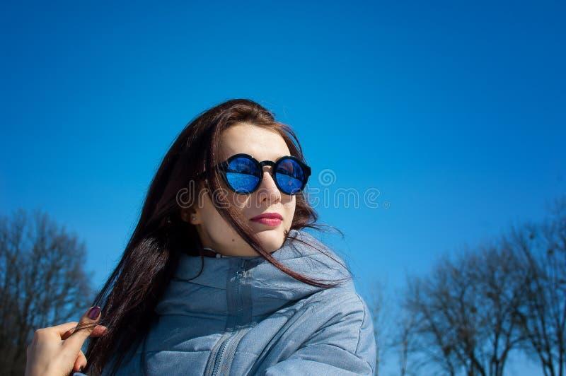 户外走在多雪的冬天公园的美女画象的生活方式关闭 微笑和享受冬天 免版税库存照片