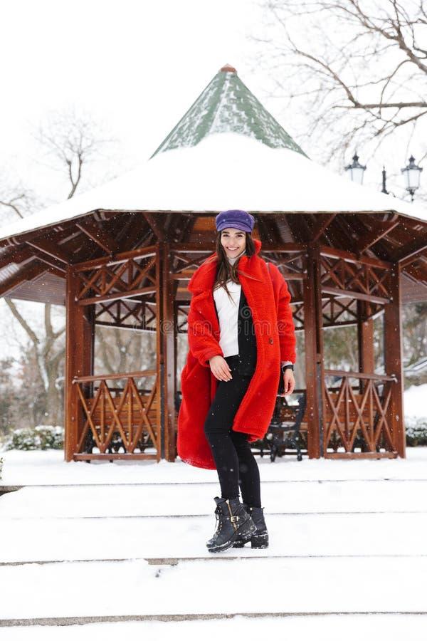 户外走在雪冬天公园森林里的令人惊讶的美丽的年轻女人 免版税图库摄影