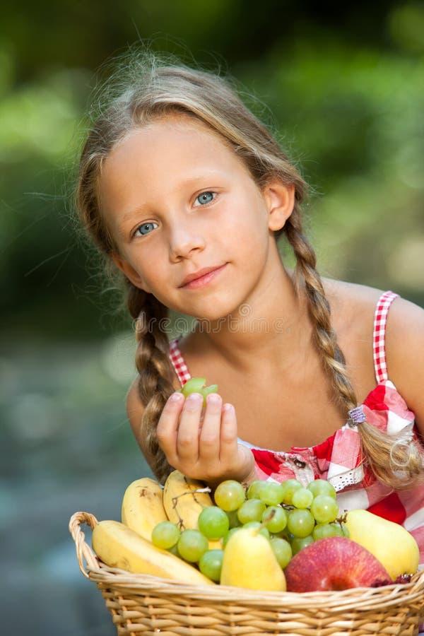 户外逗人喜爱的女孩wih新鲜水果篮子。 免版税库存照片