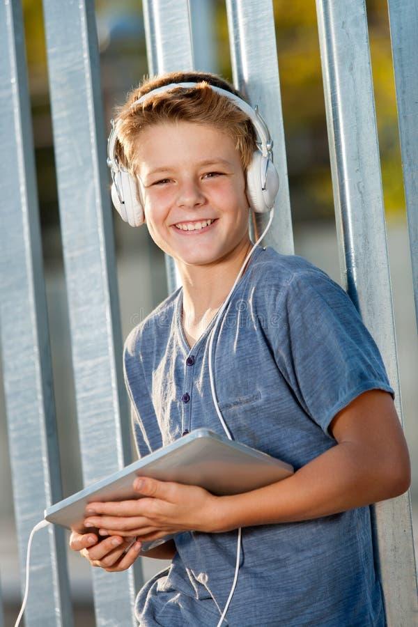 户外逗人喜爱的青少年的男孩藏品片剂。 免版税库存图片