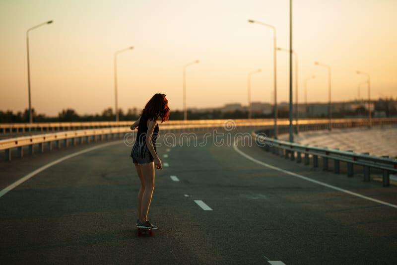 户外都市时兴的女孩骑马longboard在日落的路 免版税库存图片