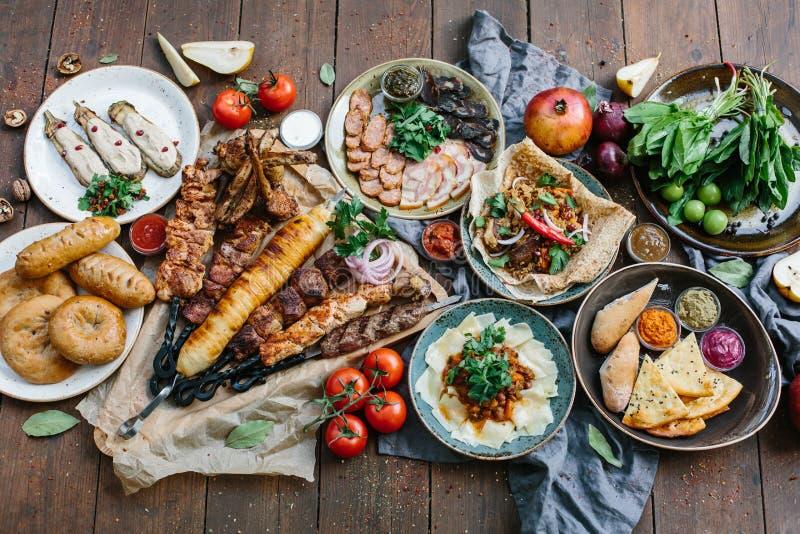 户外食物概念 开胃烤牛排、香肠和烤菜在一张木野餐桌上 免版税库存图片