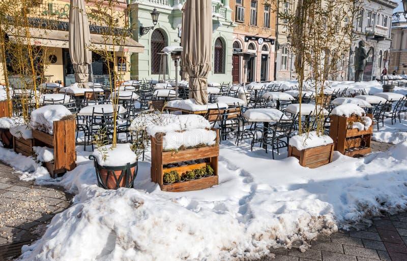 户外餐馆和用在街道上的雪和椅子盖的咖啡馆桌在冬天季节 免版税库存图片