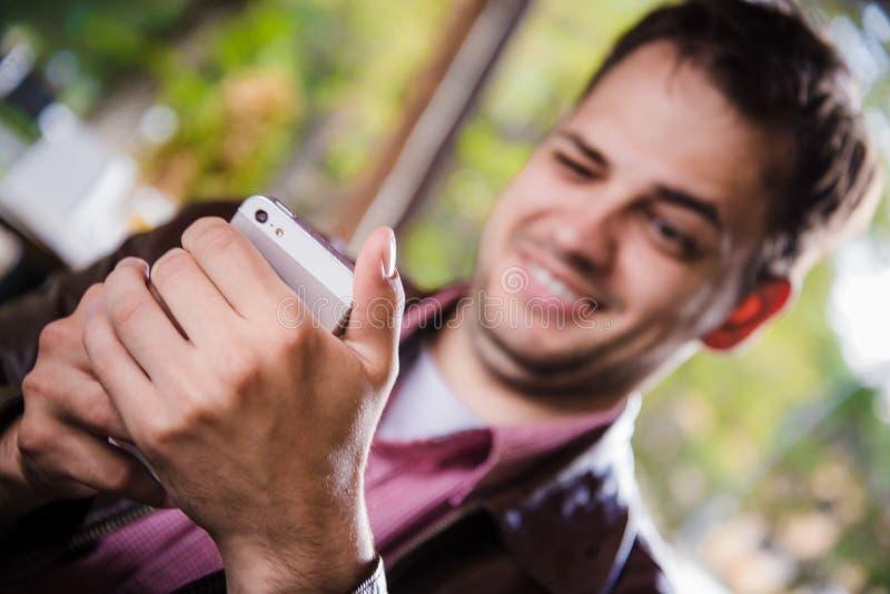 户外餐馆的快乐的人使用一个手机,手关闭  库存照片