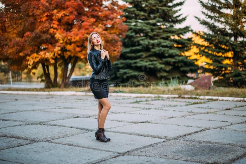 户外黑短的礼服和皮夹克的性感的美丽的妇女 库存图片