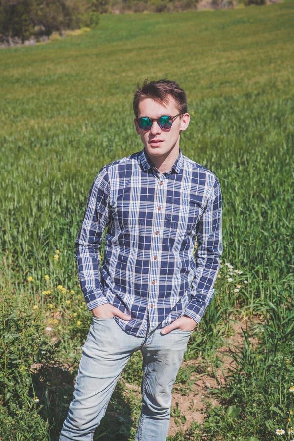 户外年轻人画象太阳镜的在乡下 免版税库存照片