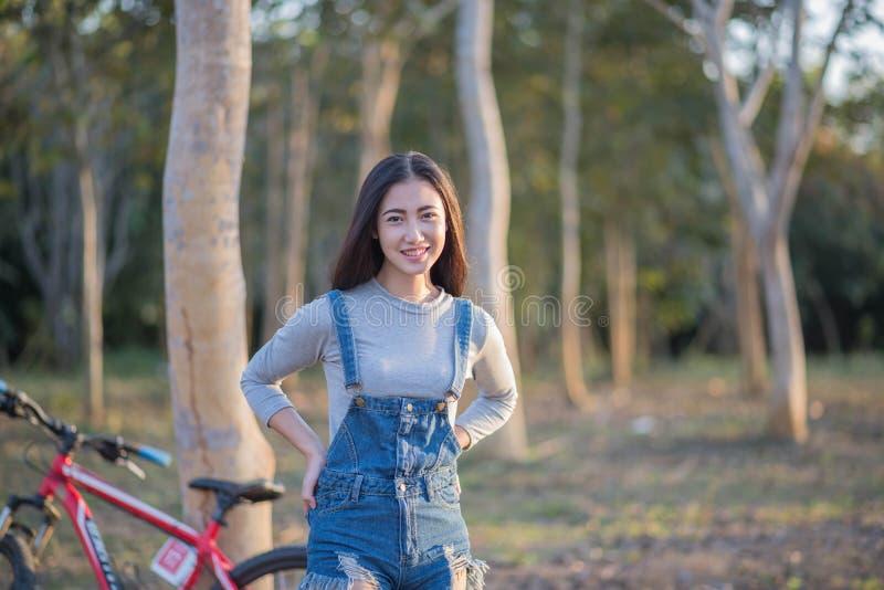 户外年轻和美丽的亚洲妇女骑马自行车在公园 库存照片