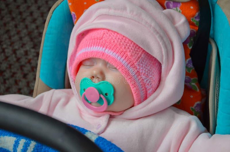 户外婴孩甜睡眠在桃红色街道穿戴 免版税库存图片