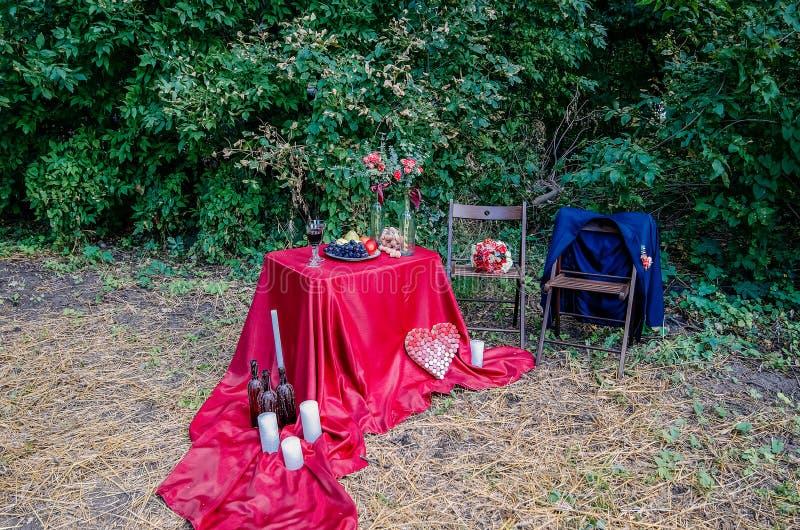 户外Edding装饰 杯酒、板材用果子和花卉装饰在桌上 免版税库存照片