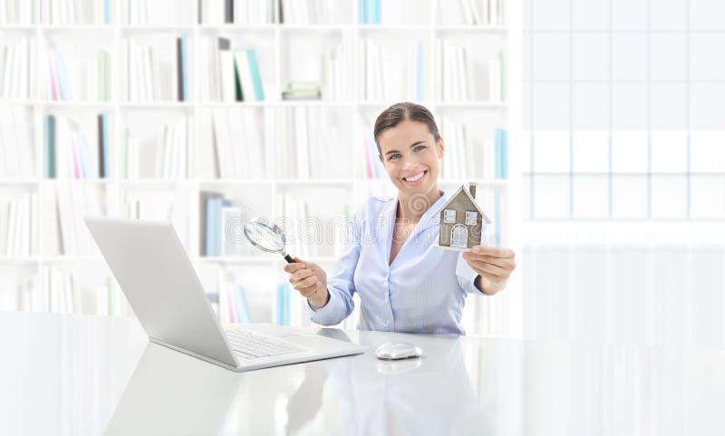 房地产办公室,研究计算机的微笑的妇女代理与 免版税图库摄影