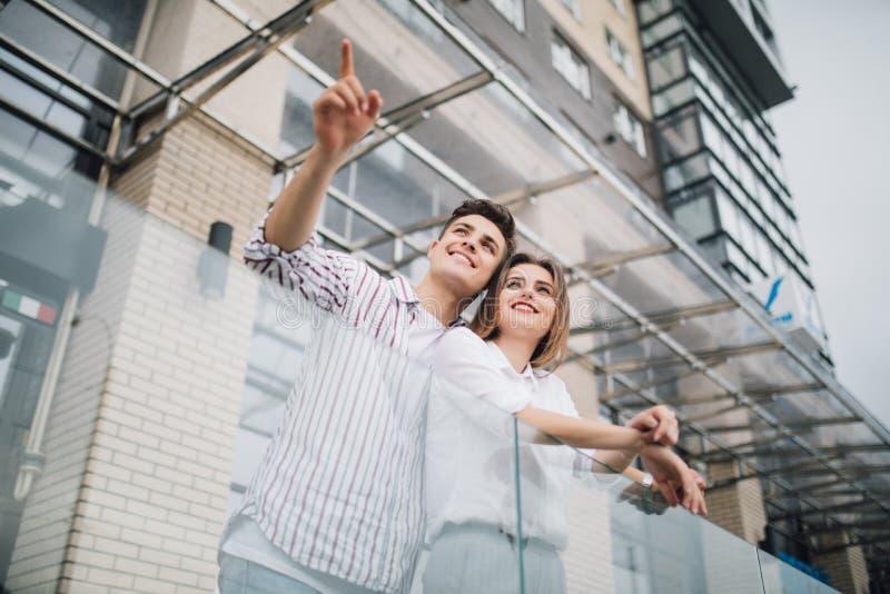 房地产和家庭观念 年轻夫妇指向了在新的大现代房子建筑前面的边  库存照片