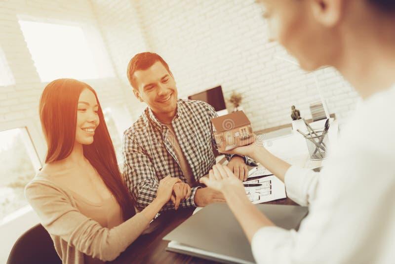 房地产机构 夫妇年轻人 议院销售 房间计划 大厦模型 为成交做准备 愉快的系列 企业生意人cmputer服务台膝上型计算机会议微笑的联系与使用妇女 库存照片