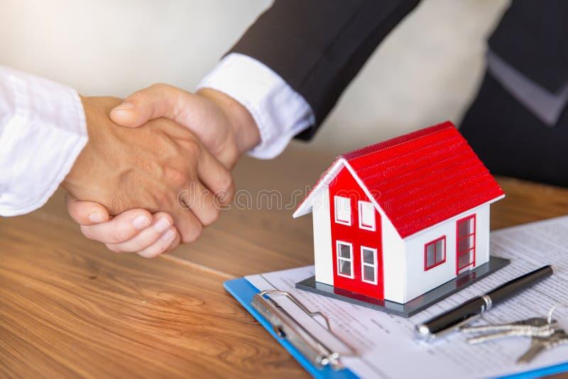 房地产经纪商与在合同签署以后,事务签署合同买进卖出房子的顾客握手,为租回家 库存图片