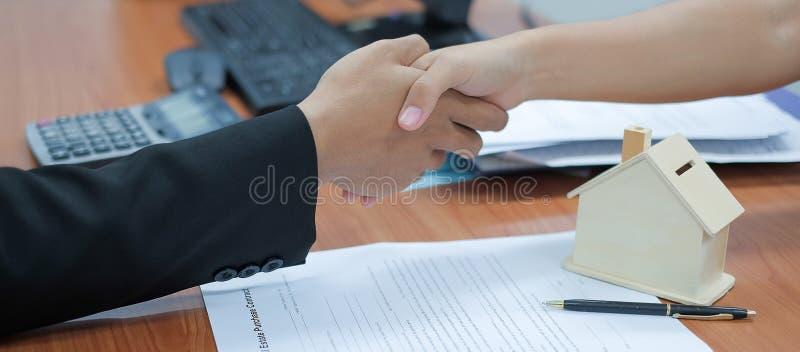 房地产经纪商与顾客握手在标志房屋贷款合同签署以后 库存照片