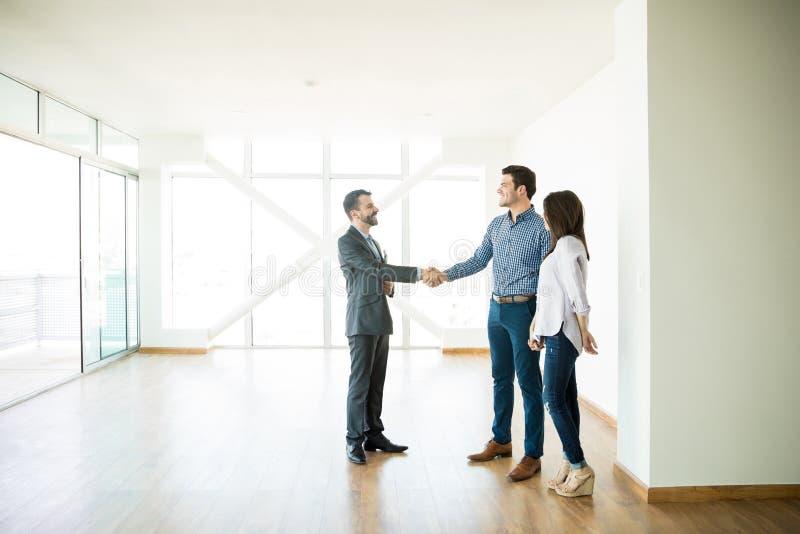 房地产经纪商在参观期间的问候夫妇到新的家 免版税库存图片
