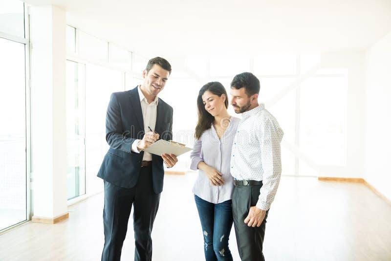 房地产经纪商夫妇的读书合同在新的家 免版税库存照片