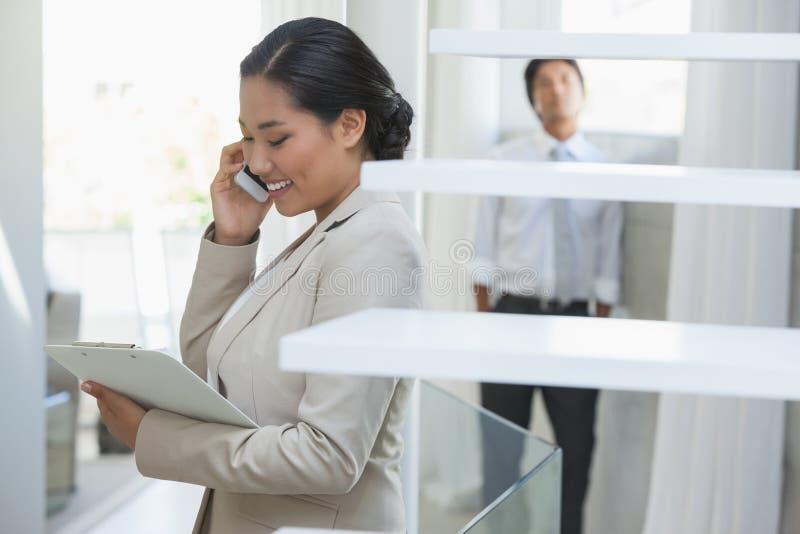 房地产经纪商谈话在有买家的电话在背景中 库存照片