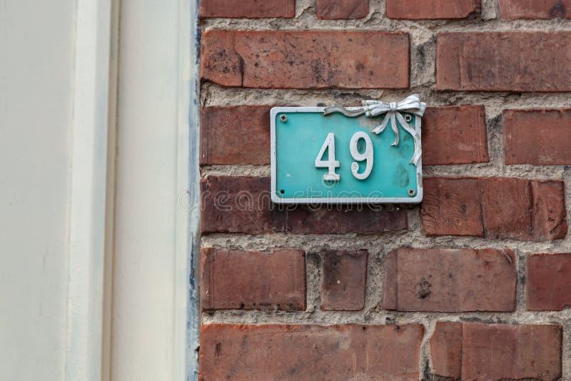 房子号码四十九49在水色背景的白色被熔铸的金属与弓 免版税库存图片