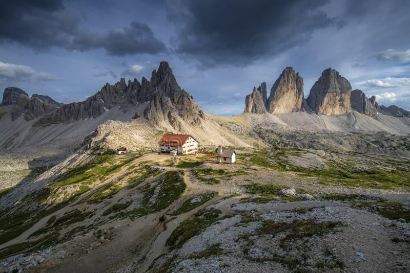 房子和山与蓝天在夏天从Tre Cime,白云岩,意大利美好的风景视图  免版税库存照片