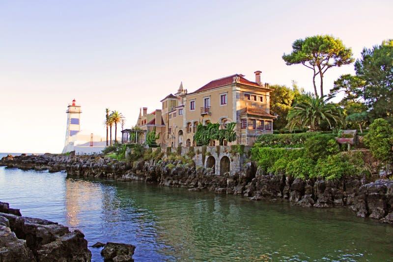 房子和灯塔在海洋 图库摄影