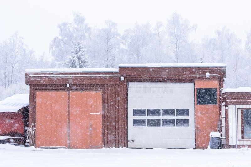 房子在森林用暴雪和坏天空盖了在冬天季节在拉普兰,芬兰 库存图片
